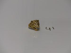 1 bague en or à décor d'une tête de lion ornée de 2 pierres rouges et d'une pierre blanche (td65). PB 18g