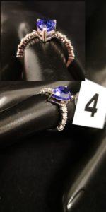 1 Bague en or gris sertie en son centre d'une tanzanite taillée en poire entre 2 lignes de 4 diamants (TD 54). PB 3,6 g