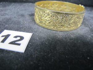 1 Bracelet en or ouvrant, large ajouré de motifs baroques ( 5,3x5,9cm). PB 26,6g