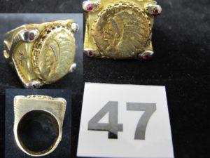 1 Chevalière imposante en or réhaussée d'un dollar americain abimé et de 4 pierres rouges aux extrémités (TD 69). PB 87,4g