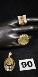 1 pendentif bicolore ajouré, 1 Bague avec plateau orné d'une gravure religieuse (TD 58) et 1 bague pavée de petites pierres blanches et noires (TD 59). Le tout en or. PB 15g