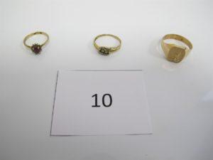 1 Chevalière en or (TD62) ornée d'une pierre blanche, 1 bague en or (TD50) rehaussée d'une pierre centrale rouge etentourage petites pierres blanches,1 bague en or(TD53)rehaussée de 3 pierres bleues.PB 6,6g.
