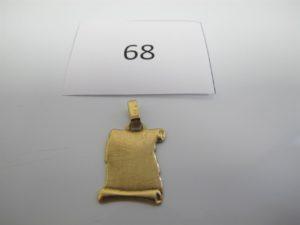 1 Pendentif en or à décor d'un parchemingravé du signe du taureau.PB 3,2g.