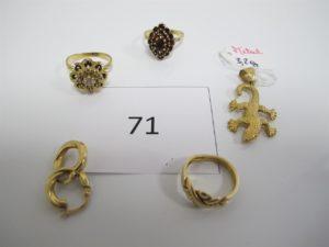 1 Bague en or rehaussée de pierres bordeaux(TD55),1 bague en or motif floral rehaussée de pierres blanches (TD58),1 bague en or motif tréssé(TD49),2 créoles en or. PB or = 13,1g+1 pendentif en métal à décor d'une salamandre pb 3,2g.