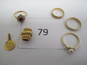 1 Bague en or rehaussée d'une pierre rouge entourée de 10 petits diamants (TD48),1 médaille d'amour en or,1 pampille en or ouvragée,1 bague en alliage 14k rehaussée d'une perle blanche et entourée de petits diamants (TD56),1 alliance alliage 14k(TD48),1 alliance alliage14k(TD56).PB total or etalliage 14k = 13,1g(or6,7g+alliage 14k