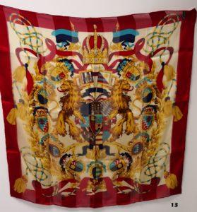 1 Foulard GIANFRANCO FERRE en soie, sur fond blanc et rouge, filigrane à rayures sur le fond représentant divers écussons et couronnes. (Dim 85x 85cm)