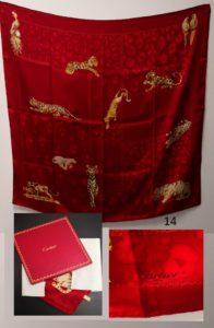 1 Foulard CARTIER, dans sa boite, en soie, dans les tons rouges à motifs animaliers (Dim 88x87cm).