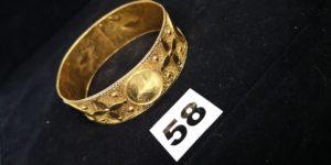 1 Bracelet en or rigide réhaussé de motif style pièce et filigrané (cabossé). PB 42,7g.
