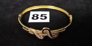 1 Bracelet en or, rigide ouvrant, orné d'un motif pavé de pierres (5,5x6cm). PB 12,4g