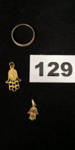 1 Alliance en or gris (TD 56) et 2 pendentifs mains de fatma dont 1 orné d'une petite pierre rose. Le tout en or . PB 3,8g