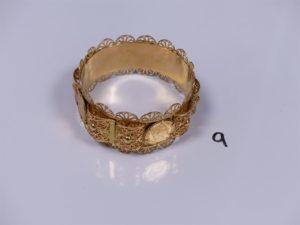 1 bracelet rigide large à motifs filigranés (1 motif cassé) serti-griffes 4 pièces de 10Frs (diamètre 7cm). PB 65,5g